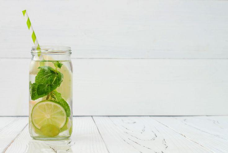 Glas mit Limette, Minze und grün-weiß gestreiften Strohhalm