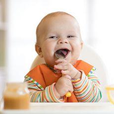 Baby mit Löffel im Mund lächelt in die Kamera