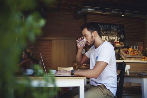 junger Mann sitzt an einem Tisch an einem Laptop und trinkt ein Glas Wasser