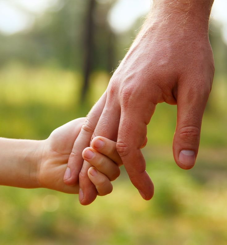 ein Kind und ein Mann halten Händchen
