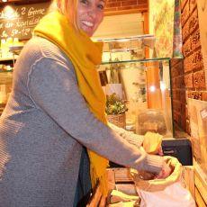 blonde Frau mit gelben Schal lacht in die Kamera