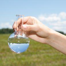 eine Hand hält ein Reagenzglas mit Wasser vor einer grünen Wiese