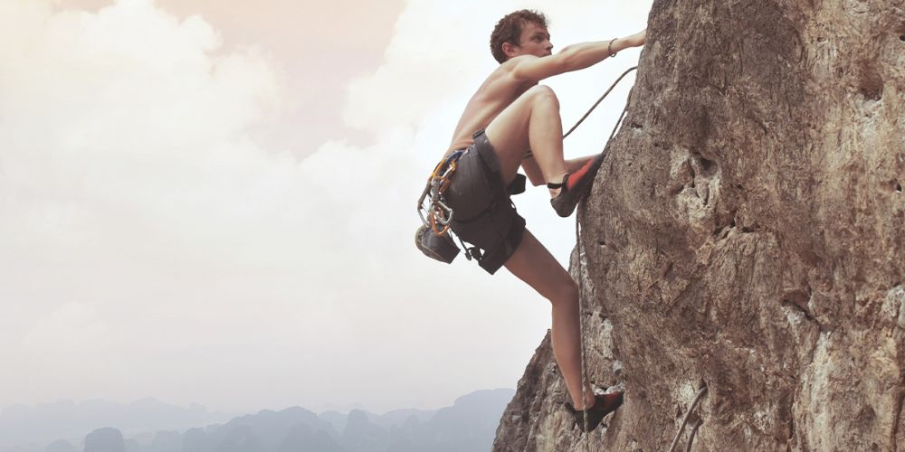 junger Mann klettert oberkörperfrei ein Berg hoch