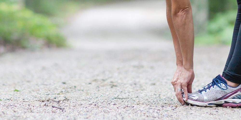 Mensch fässt sich im Stehen an die Fußspitzen