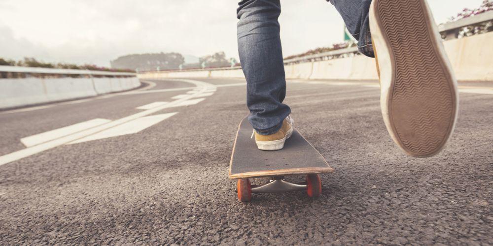 Mensch fährt ein Skateboard auf einer Straße