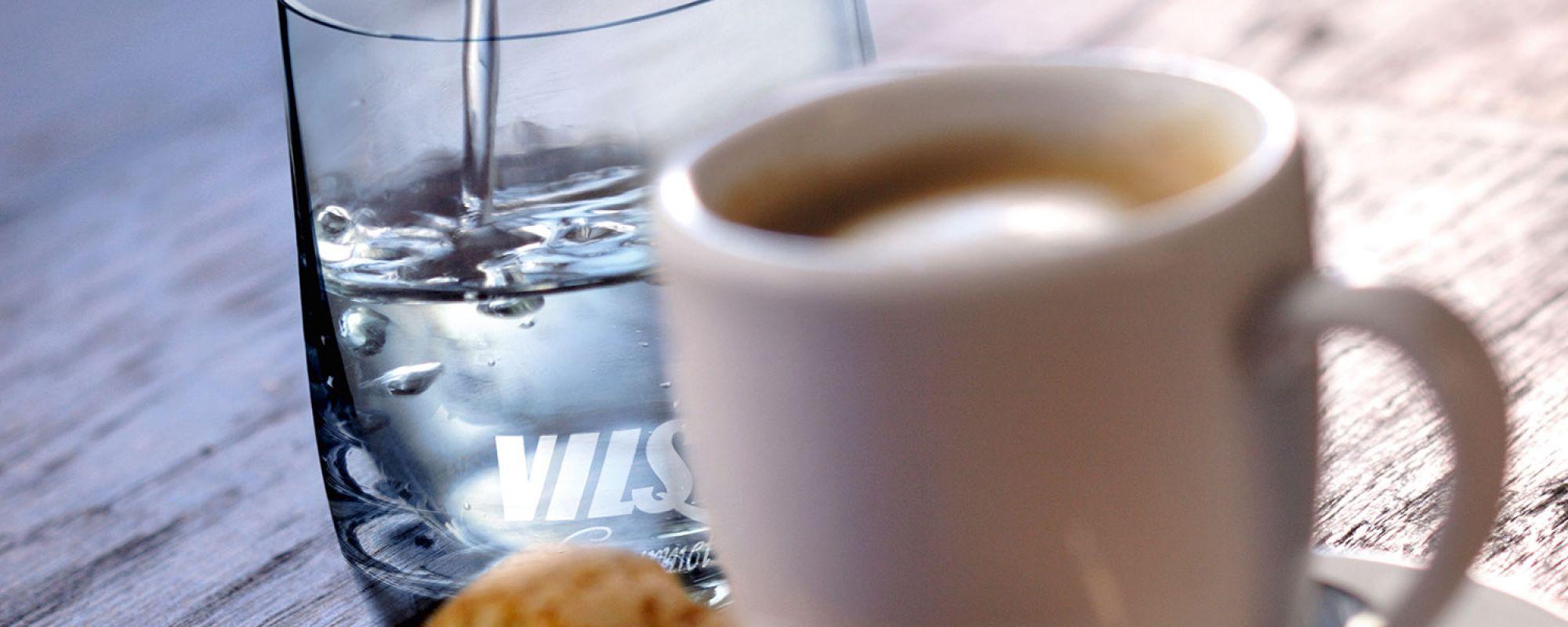 VILSA Mineralwasser neben einer Tasse Kaffee