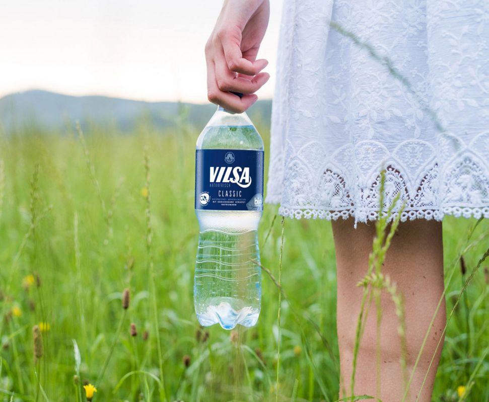 Frau mit weißem Kleid hält VILSA Mineralwasser classic rPET 1,0l in einem grünen Feld in der Hand