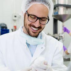 Mann im Laborkittel mit Brille lacht, auf der rechten Bildseite befindet sich das Institut Fresenius Logo