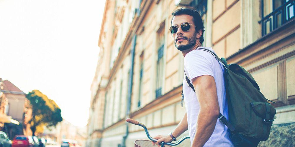 junger Mann mit dunklen Haaren, Sonnenbrille und helllila T-Shirt schiebt ein Fahrrad und guckt in die Ferne