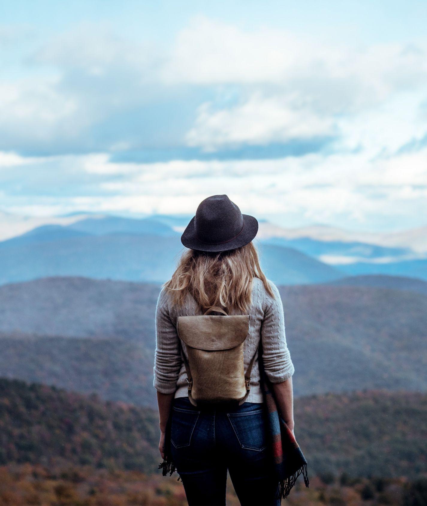 Frau mit Hut und Rucksack schaut auf eine Berglandschaft