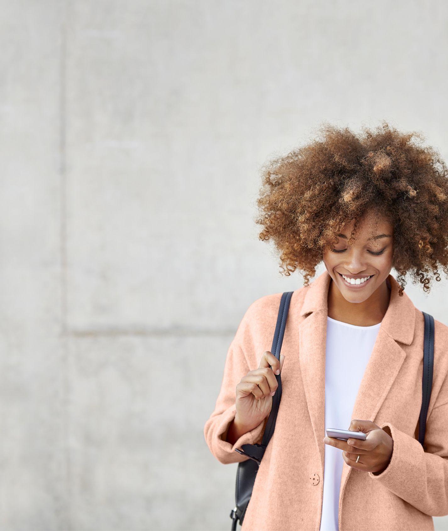 junge Frau mit peachfarbenden Mantel schaut lächelnd auf ihr Handy