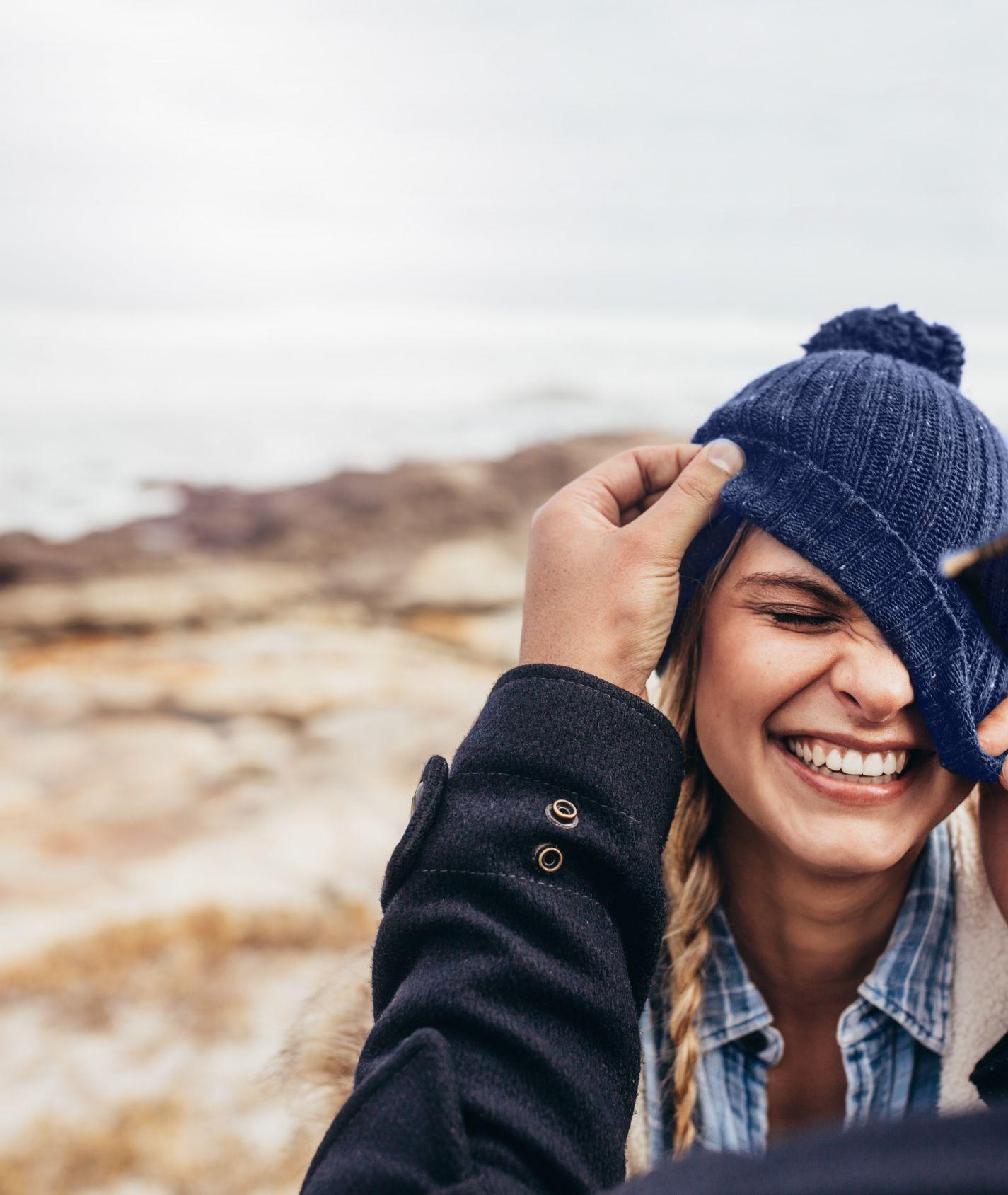 junge lachende Frau mit dunkelblauer Mütze