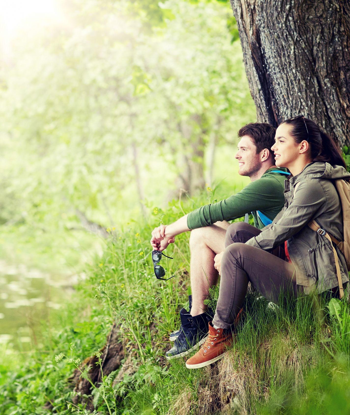 ein junger Mann und eine junge Frau sitzen an einem Ufer und schauen in die Ferne