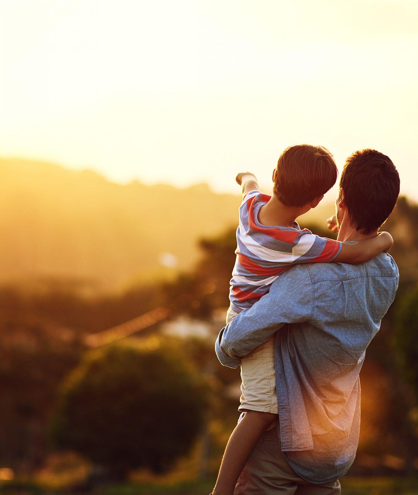 Vater hält Kind auf dem Arm und schaut in die Ferne