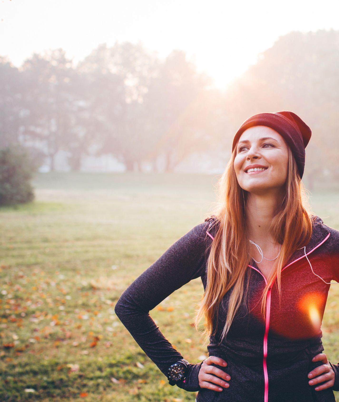 junge Frau mit organen Haaren, roter Mütze und Sportjacke hat die Hände in die Hüfte gestemmt und steht auf einer Wiese