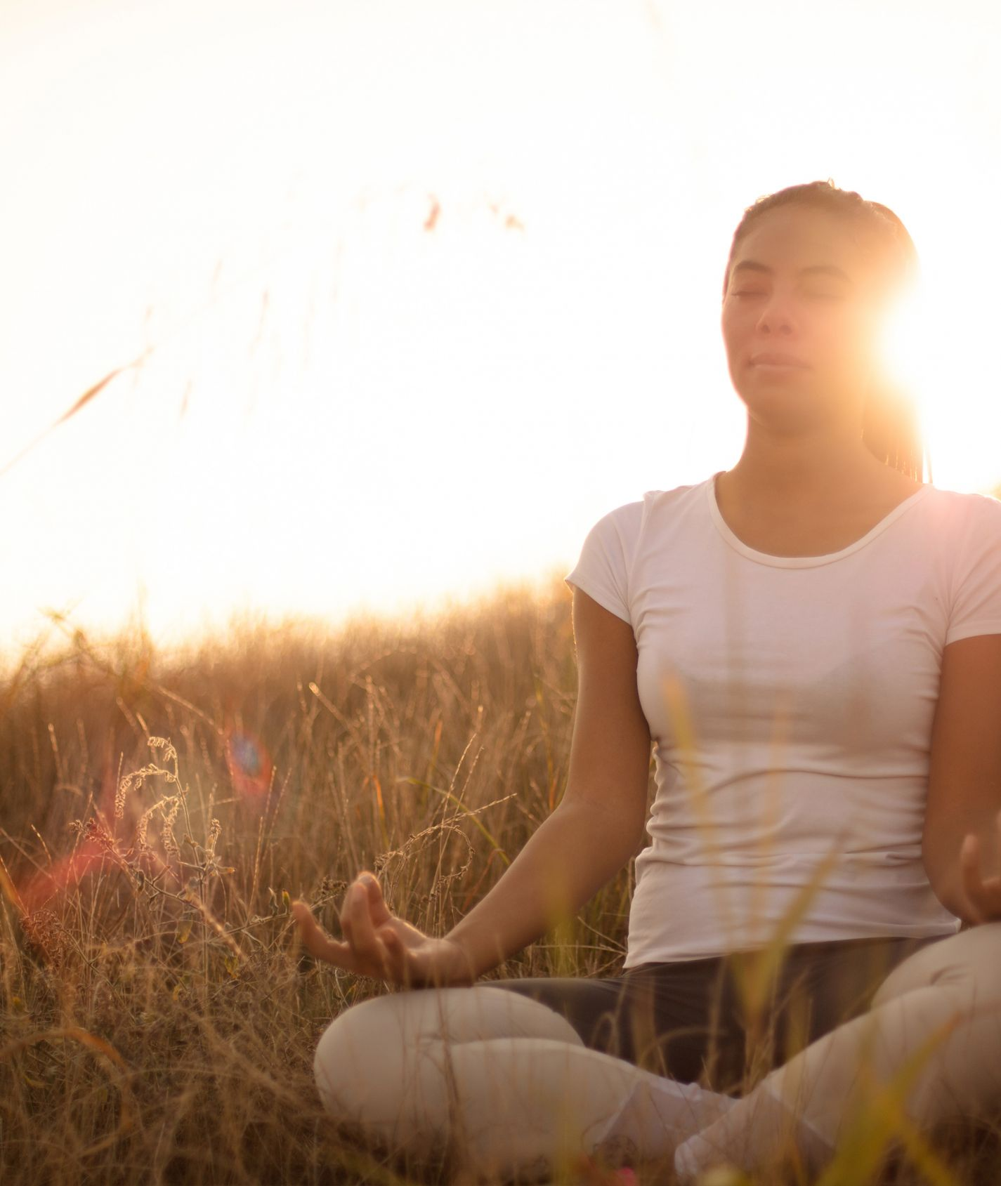 junge Frau sitzt im Jogasitz auf einem Weizenfeld