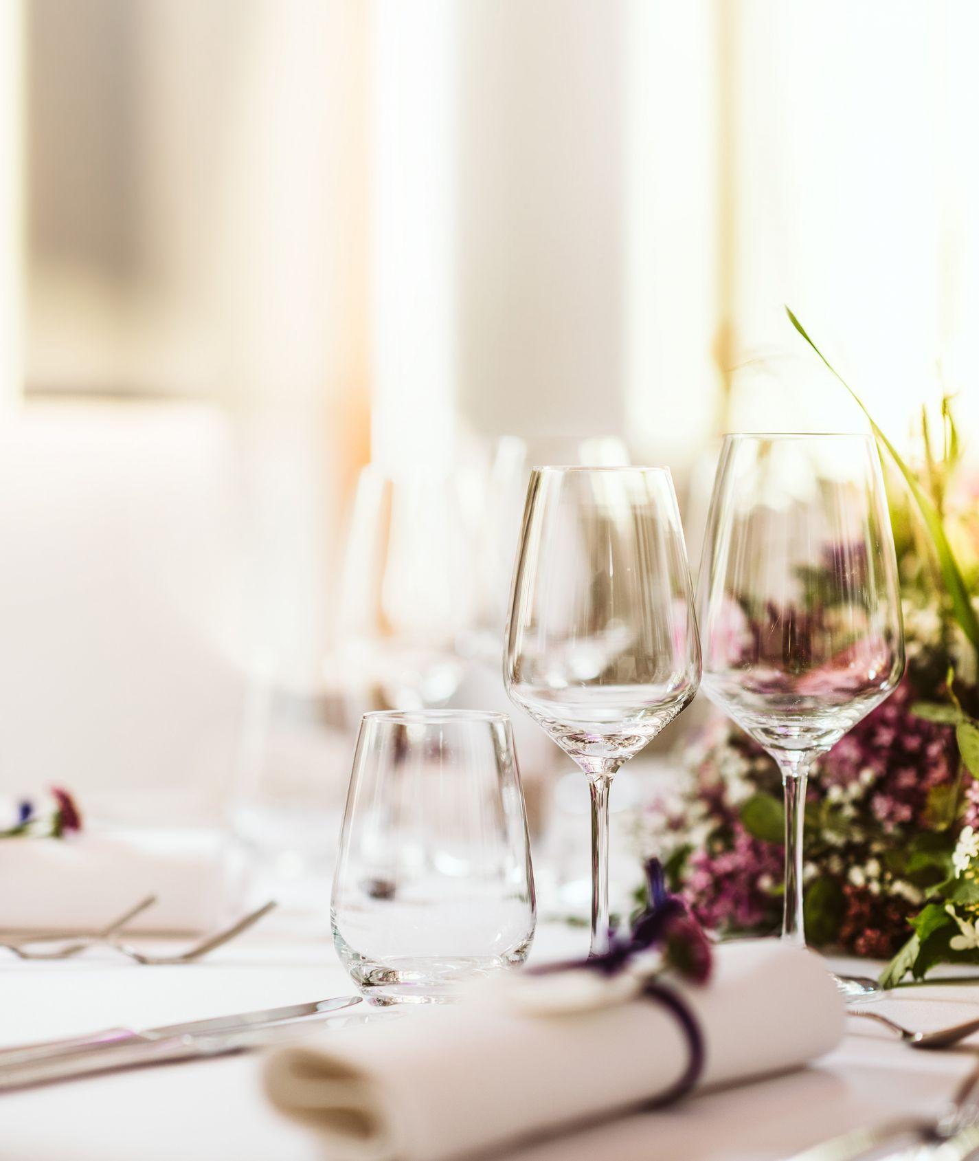 Tisch mit weißer Decke mit Wasserglas und Weinglas