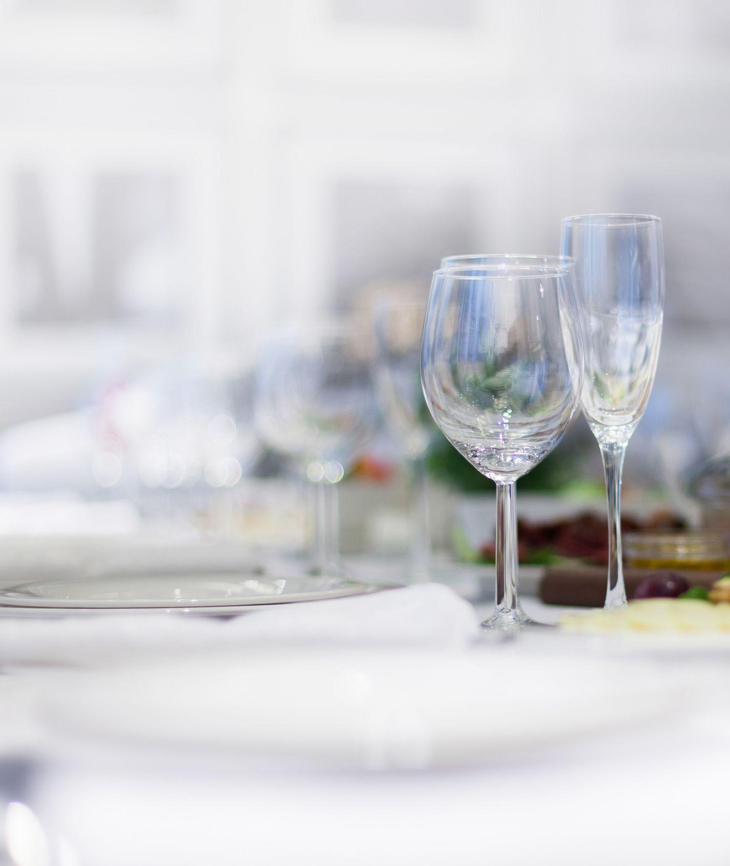 Tisch mit weißer Decke mit Wasserglas und Sektglas