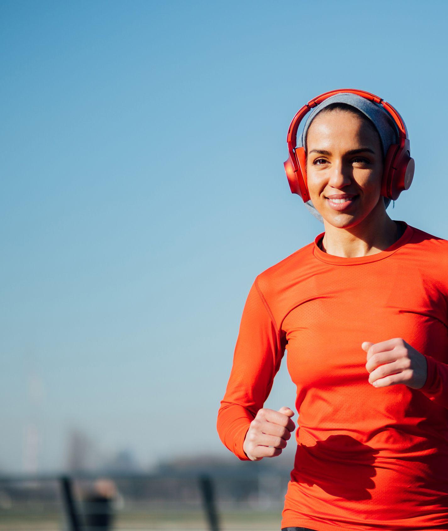 junge joggende Frau mit orangem Langarmshirt und roten Kopfhören