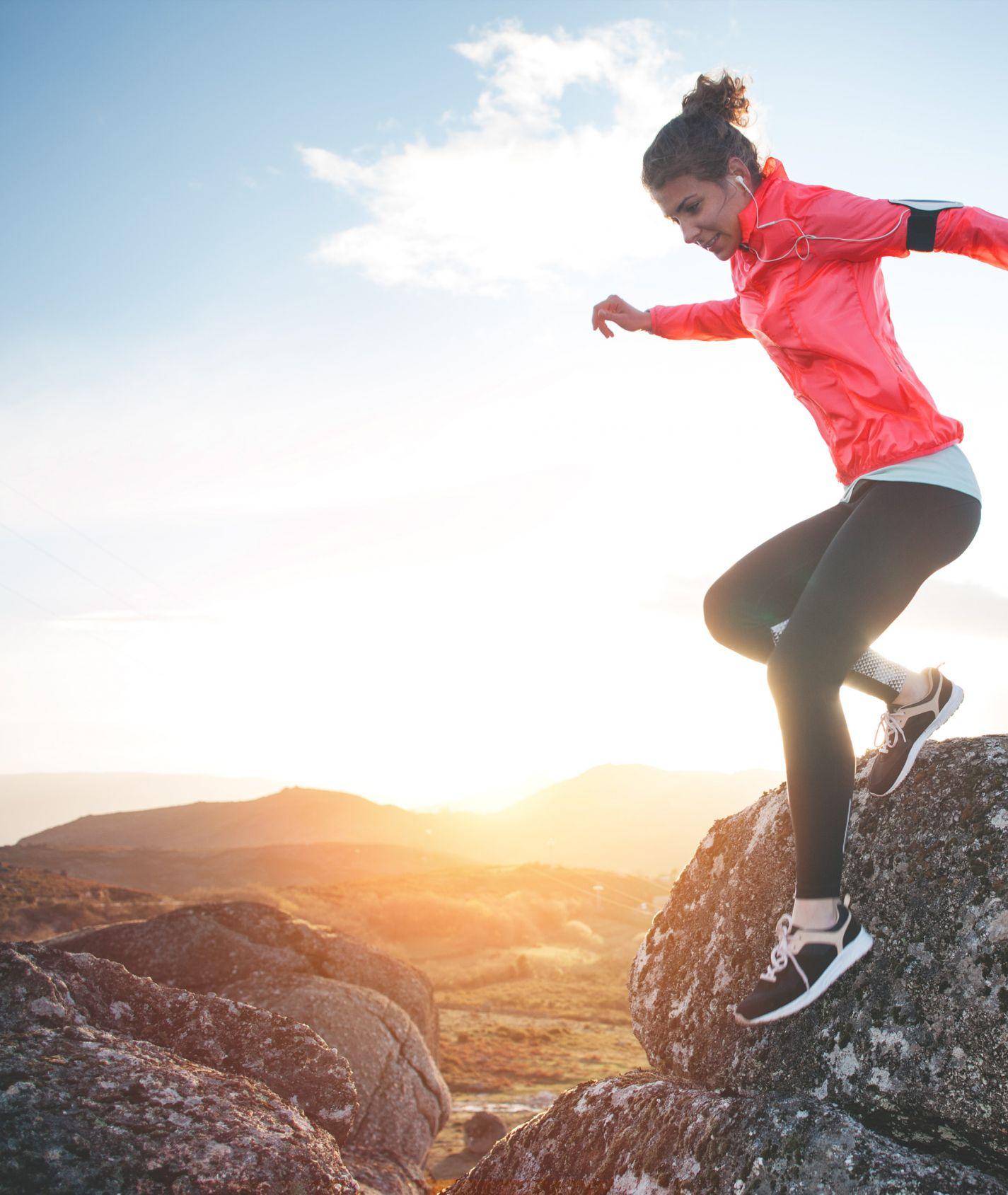 junge Frau mit pinker Jacke und schwarzer Sportleggings klettert in den Bergen