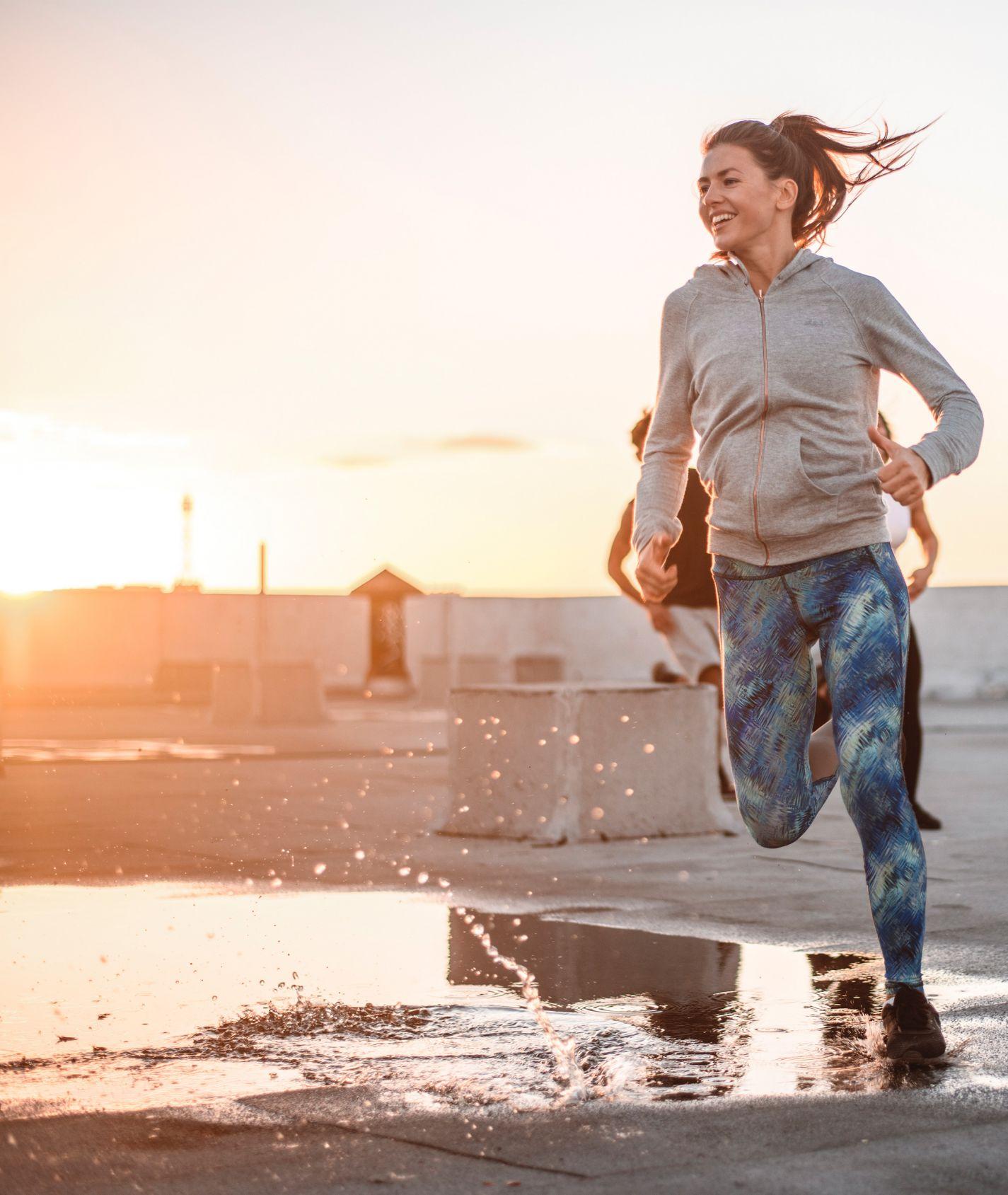 junge Frau mit grauer Jacke und blauer Sportleggings joggt im Sonnenschein durch eine Pfütze