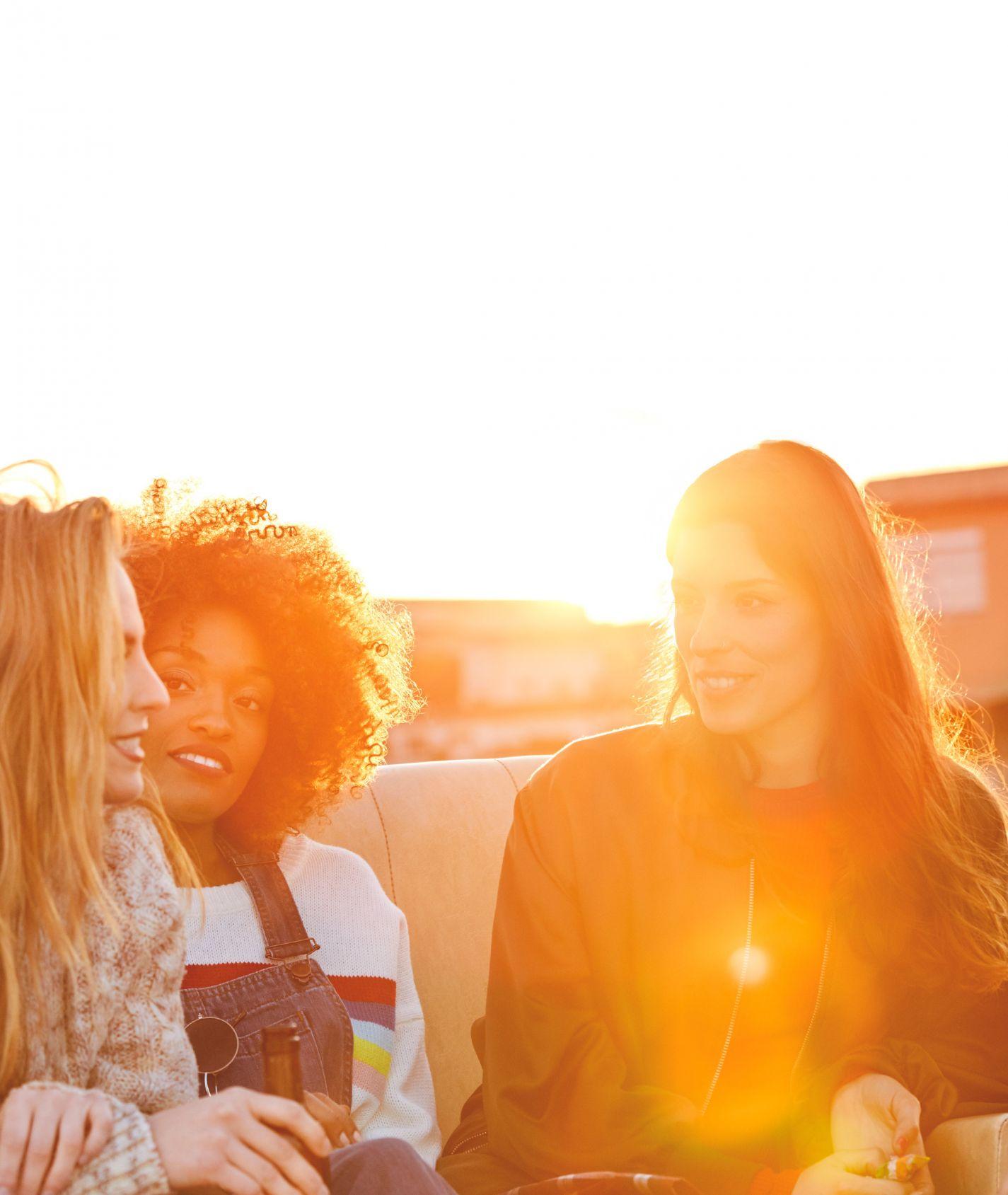 drei junge Frauen unterhalten sich im Sonnenschein