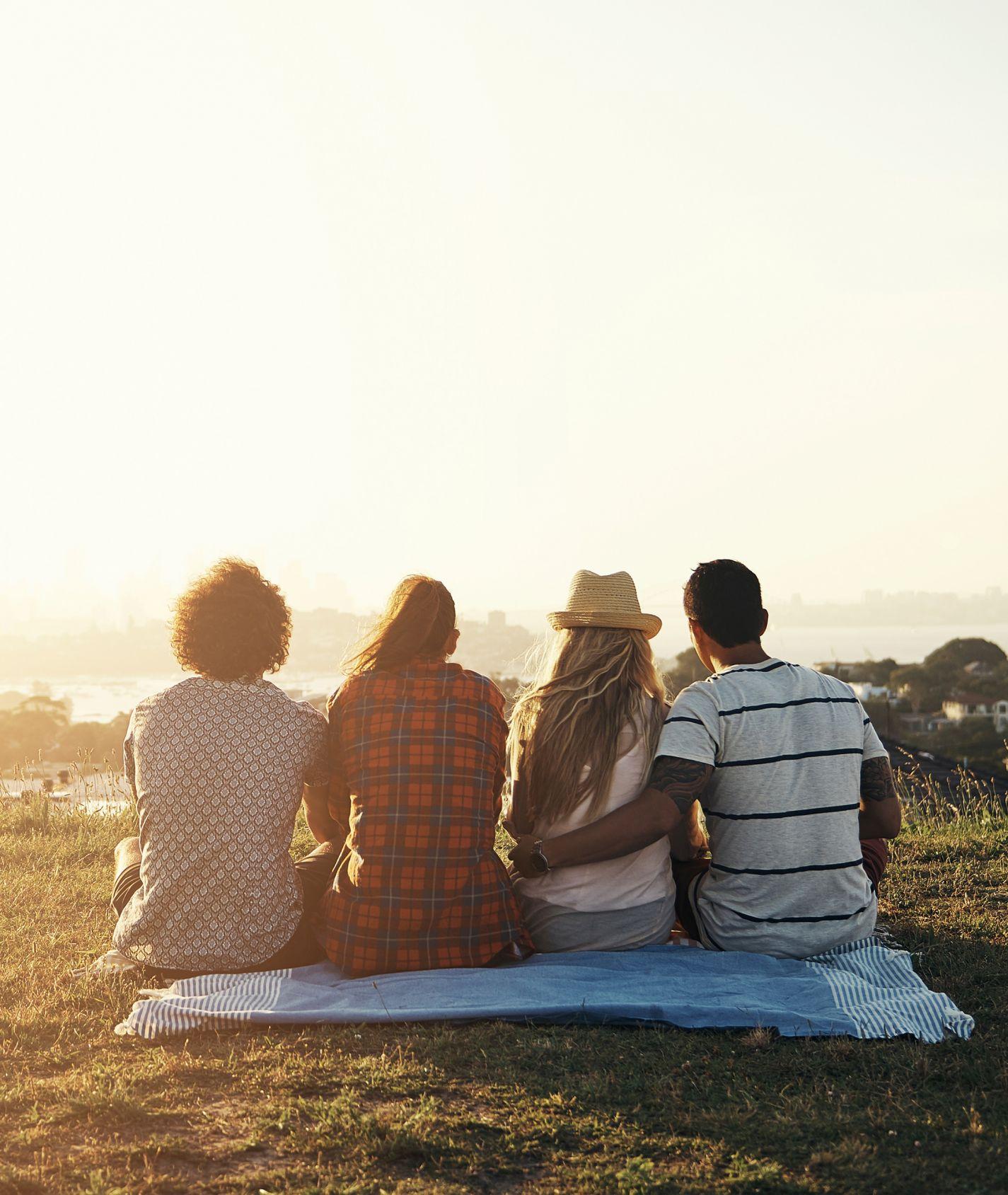 vier junge Menschen schauen in die Ferne und sitzen auf einer Wiese