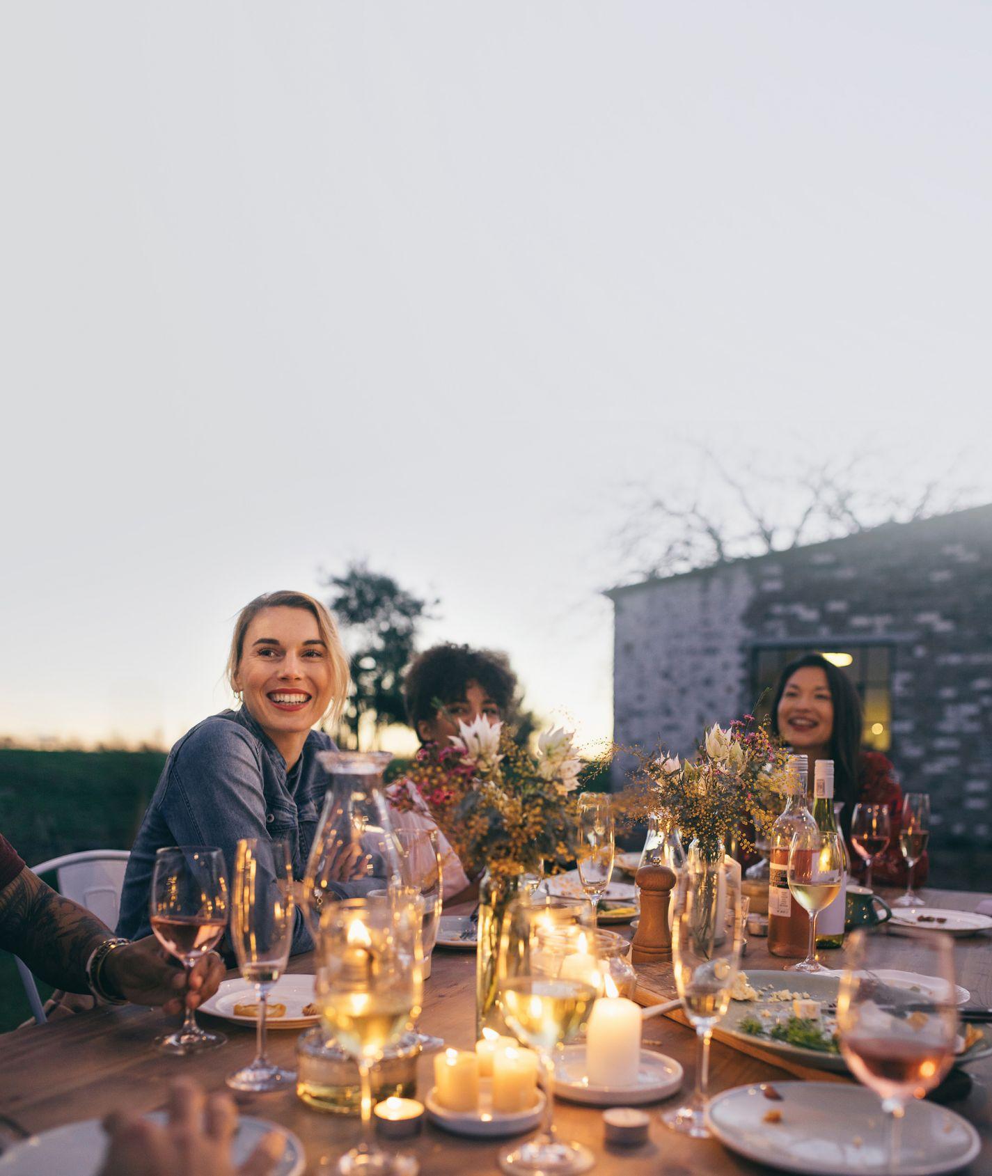 Eine Gruppe junger Frauen sitzen in der Abenddämmerung an einem Tisch und lachen