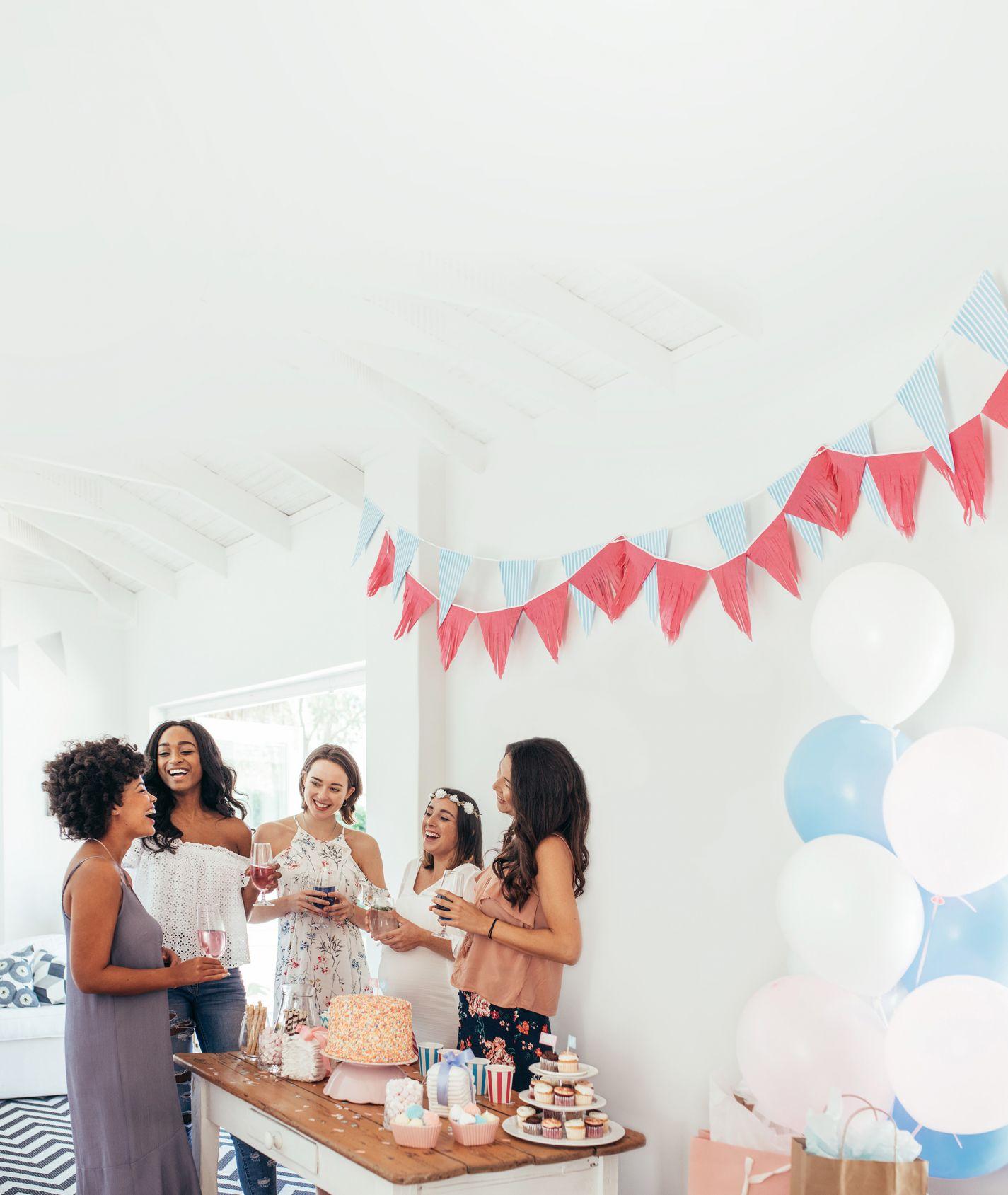 Eine Gruppe junger Frauen stehen um einen Geburtstagstisch herum und lachen