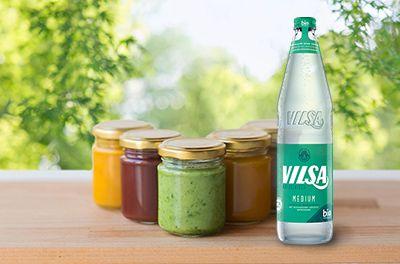 VILSA Mineralwasser medium 0,7l Glas auf einem Holztisch mit diversen Gläsern