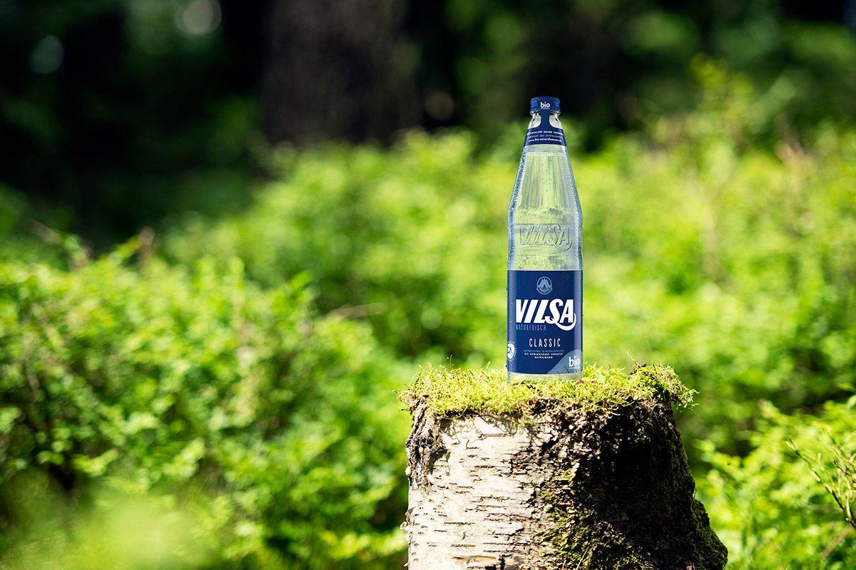 VILSA Mineralwasser classic Glas 0,7l auf einem Baumstumpf in der Natur