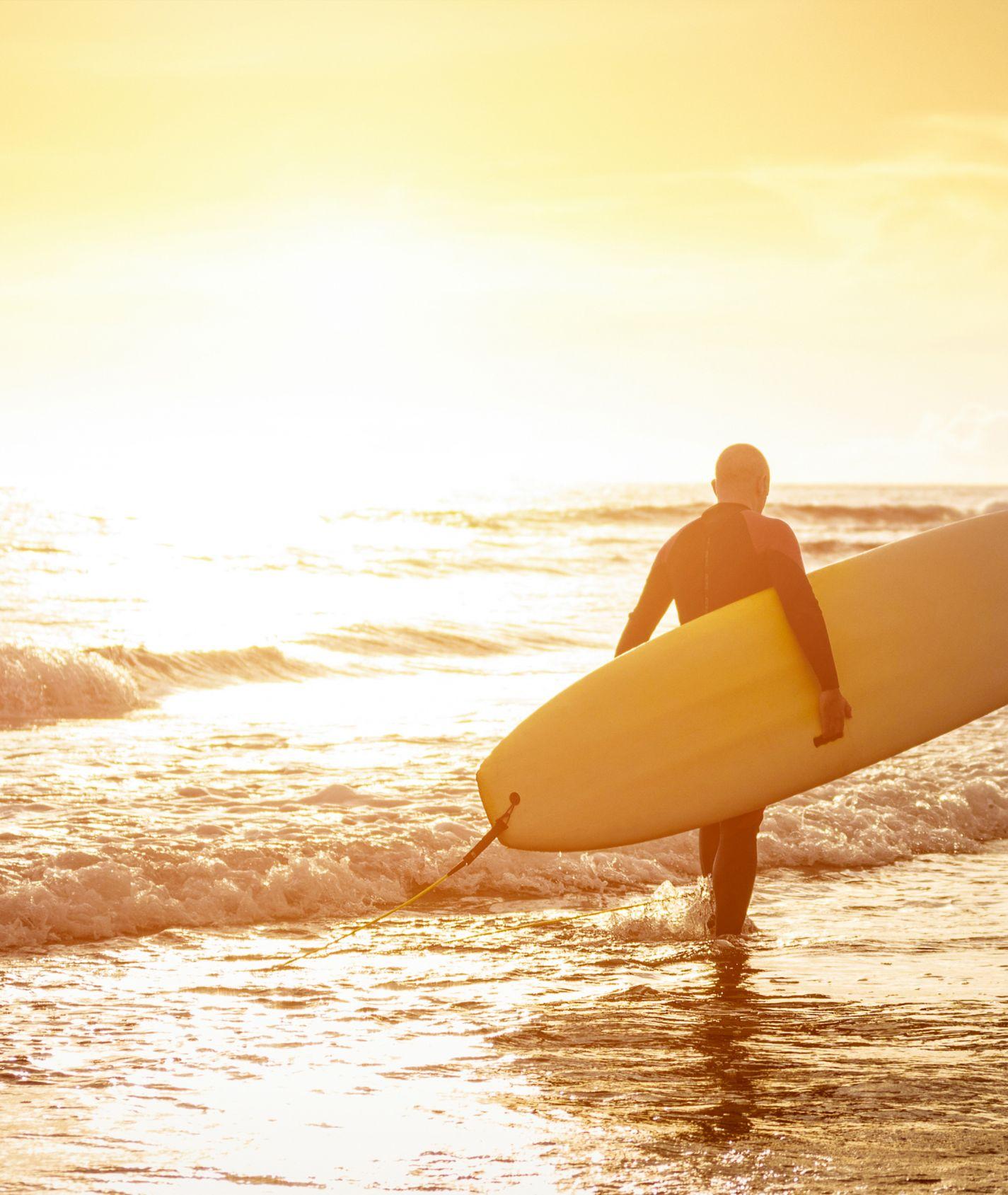 Mann mit Surfboard geht ins Meer bei Sonnenschein.