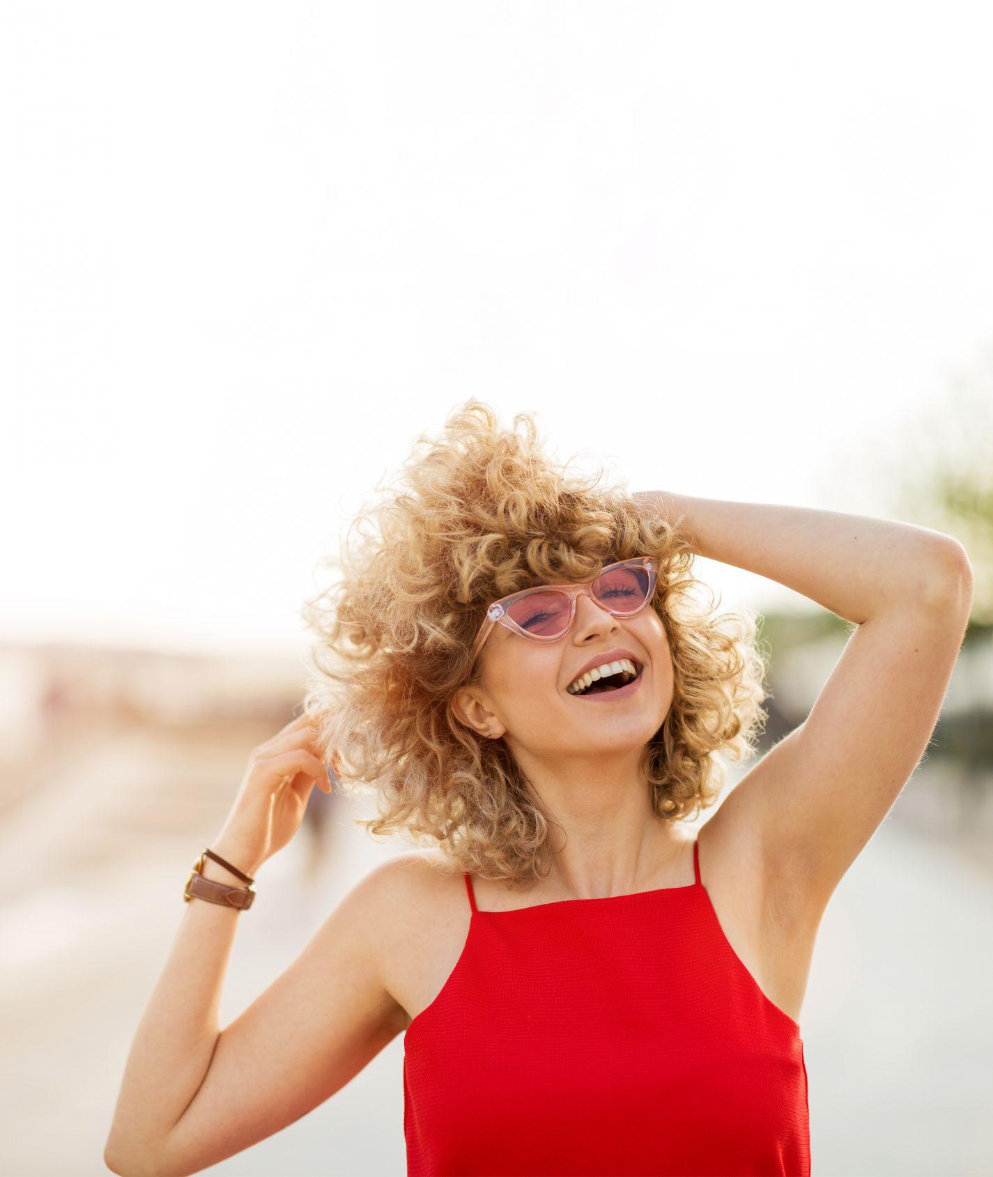 lachende junge Frau mit blonden Locken, rosa Sonnenbrille und rotem Oberteil fasst sich in ihre Haare