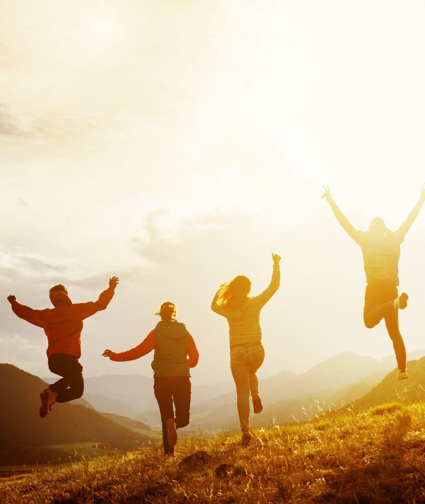 springende Familie in der einer sonnigen Berglandschaft