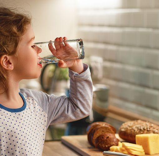 kleines Mädchen trinkt Wasser aus einem Glas in der Küche
