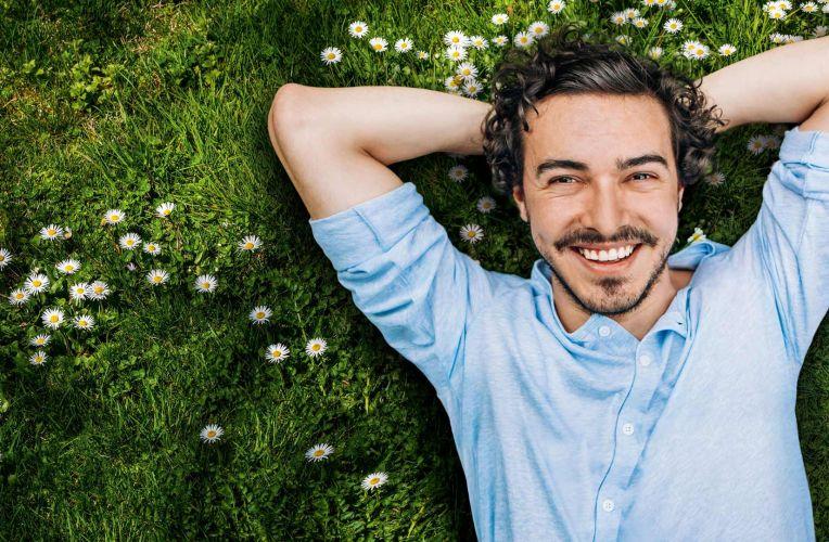 junger Mann mit schwarzen Haaren und blauen Hemd schaut in die Kamera und liegt auf einer grünen Wiese mit Gänseblümchen