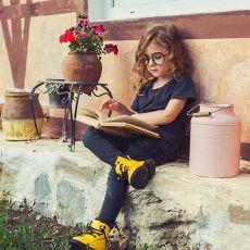 kleines Mädchen mit Brille liest ein Buch auf einer Mauer