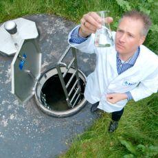 Labormitarbeiter entnimmt Mineralwasserprobe
