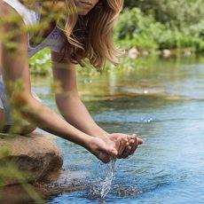 Frau schöpft mir ihren Händen Wasser aus einem Bach