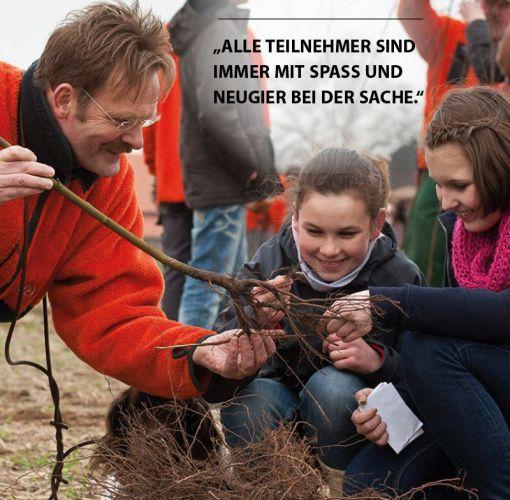 Franz Hüsing zeigt Kindern im Schulwald eine Wurzel