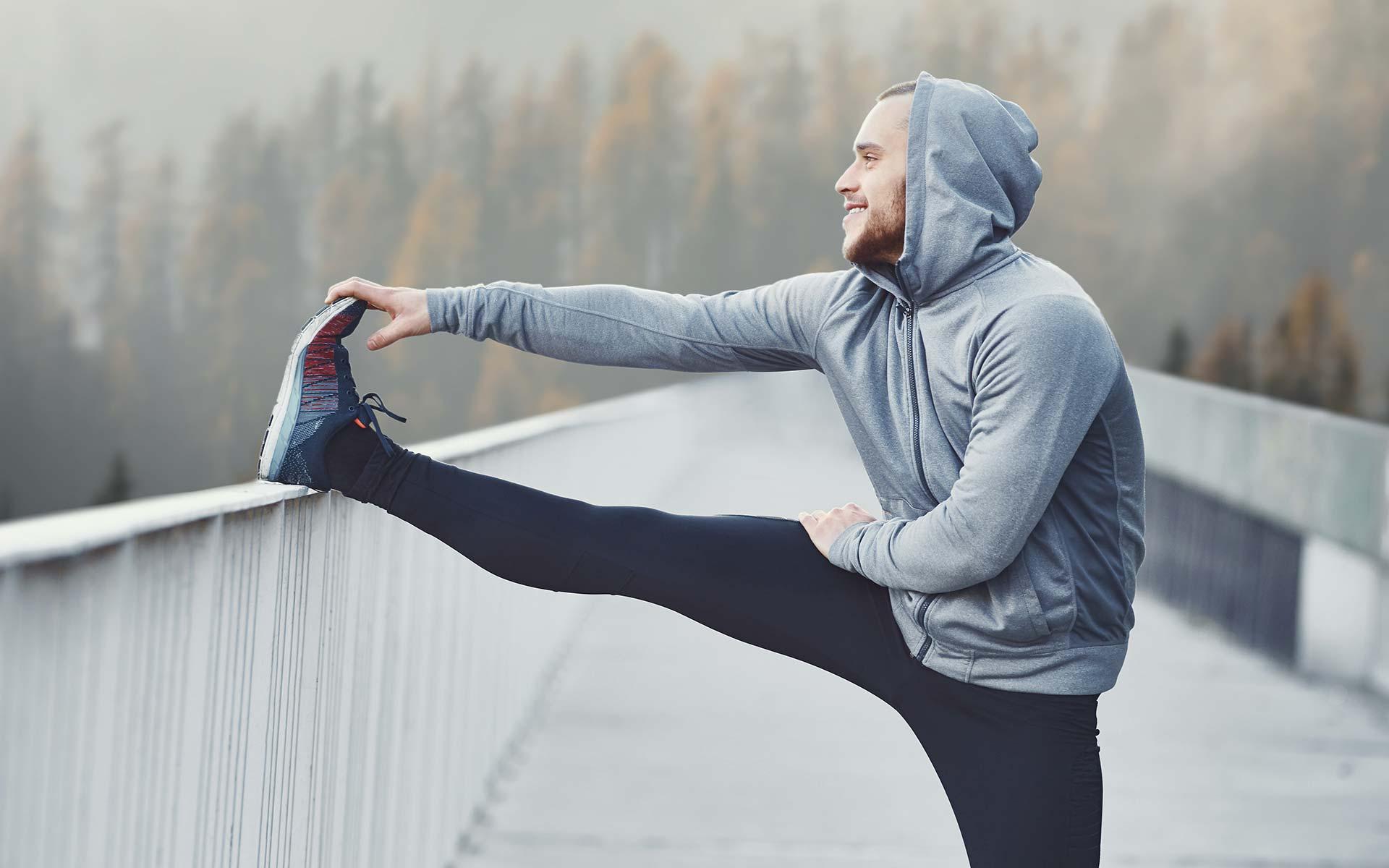 junger Mann mit grauer Sportjacke dehnt sich mithilfe eines Brückengeländers