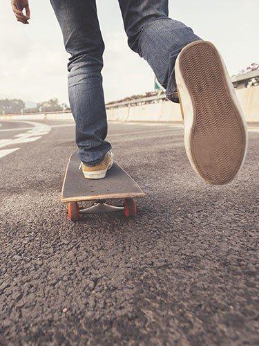Mensch fährt auf einem Skateboard auf einer Straße