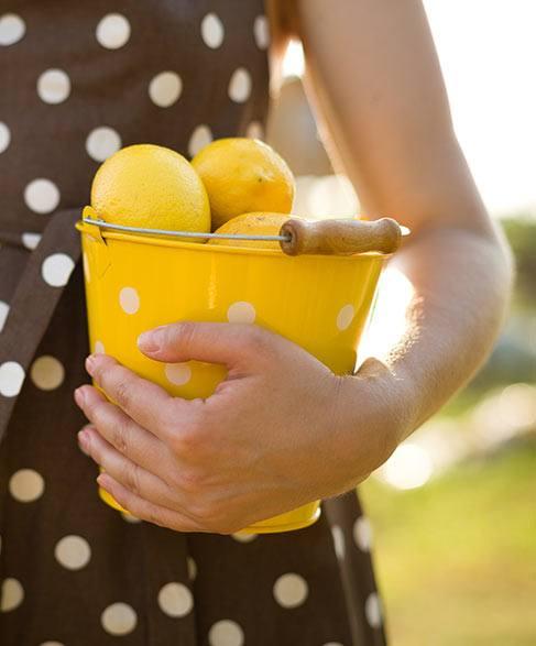 Frau hält einen mit zitronengefüllten gelben Eimer mit weißen Punkten