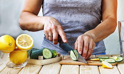 Frau schneit Gurken und Zitronen