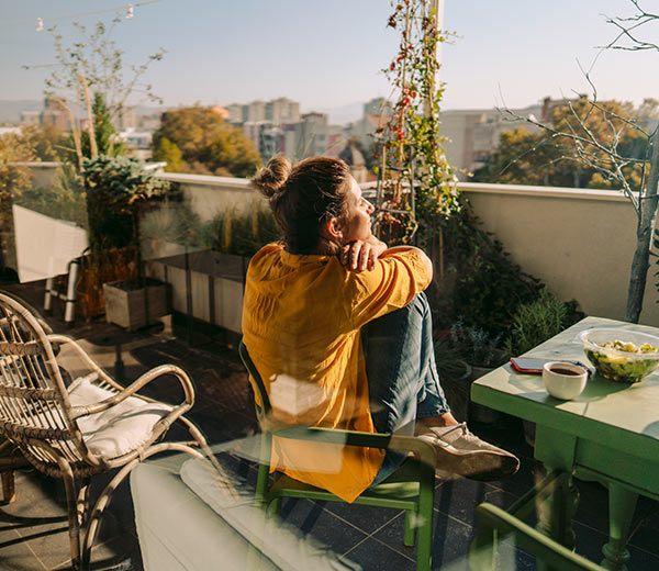Frau sitzt auf einem Balkon in der Sonne