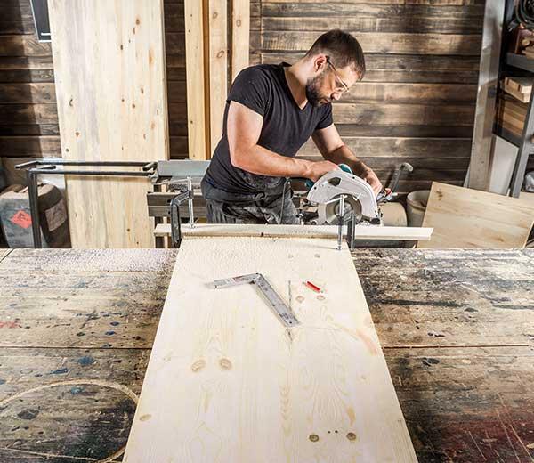 Mann schneidet Holz mit einer elektrischen Holzsäge