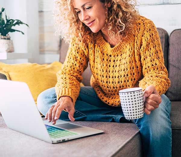Frau mit gelbem Pulli sitzt auf einer Couch und guckt auf einen Laptop