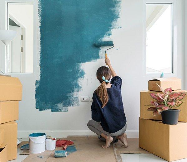 eine Frau streicht eine weiße Wand petrolblau