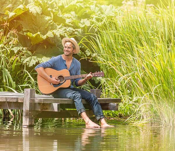 junger Mann sitzt auf einem Holzsteg und spielt auf einer Gitarre
