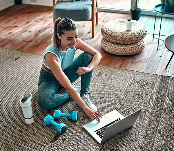 Frau mit Sportklamotten sitz mit Laptop auf einem Teppich
